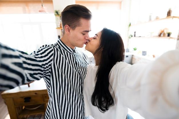 Jeune couple attrayant s'embrasser et prendre selfie Photo gratuit