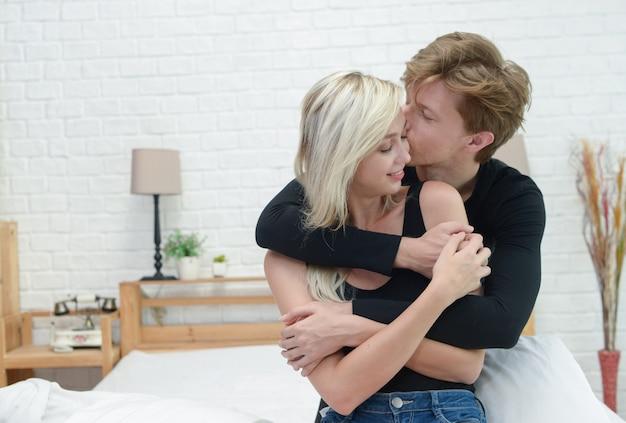 Jeune couple au lit ensemble. couple romantique amoureux se regardant. Photo Premium