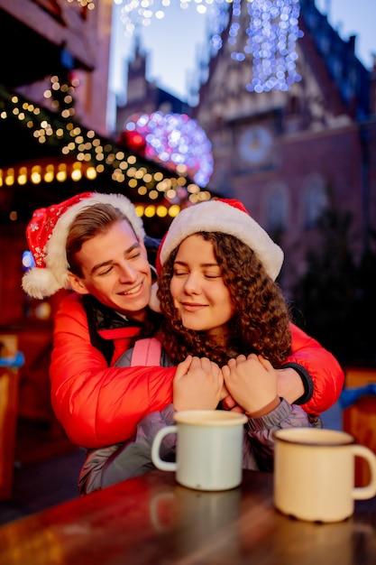 Jeune couple avec boissons sur le marché de noël à wroclaw, pologne Photo Premium