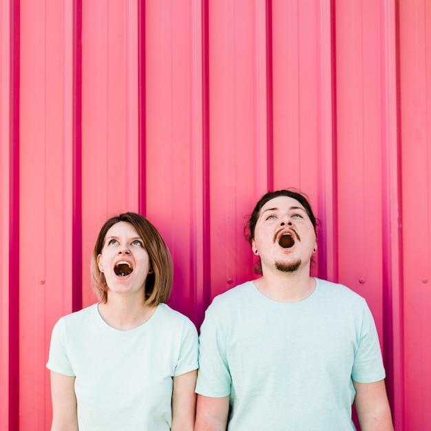Jeune couple, bouche ouverte, lever, rose, ondulé, fer Photo gratuit