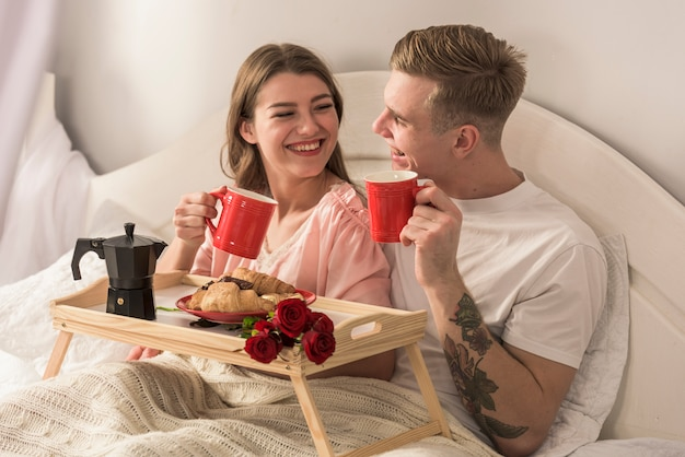 Jeune couple buvant du café au lit Photo gratuit
