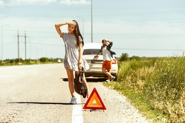 Le Jeune Couple A Cassé La Voiture Alors Qu'il Se Rendait Au Repos. Photo gratuit
