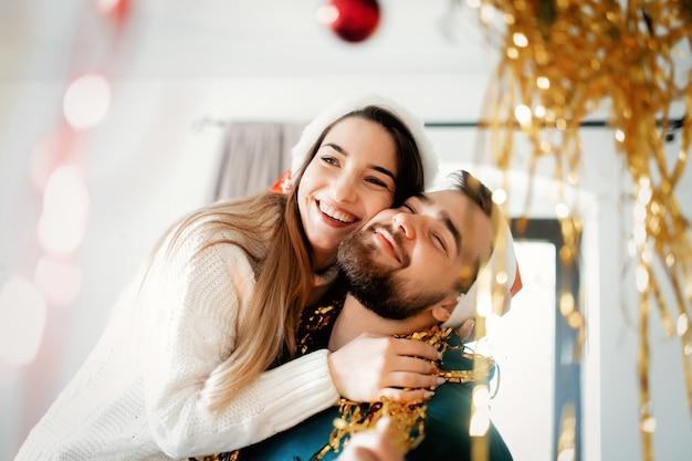 Jeune couple en chapeaux de noël décore la maison pour noël et nouvel an Photo Premium