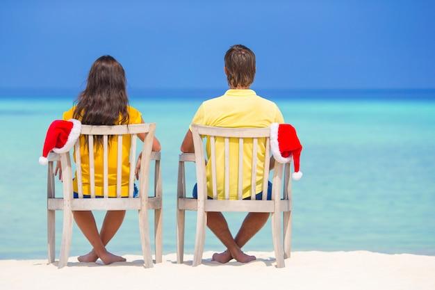Jeune couple en chapeaux santa se détendre sur une plage tropicale pendant les vacances de noël Photo Premium