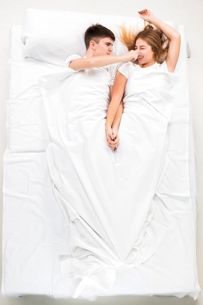 Le Jeune Couple Charmant Couché Dans Un Lit Photo gratuit