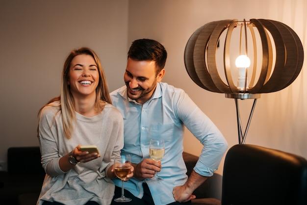 Jeune couple cherche téléphone mobile et rire. Photo Premium