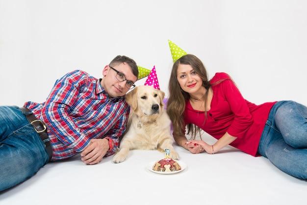 Jeune Couple Et Un Chien Retriever En Chapeau D'anniversaire Et Gâteau Avec Bougie. Photo Premium