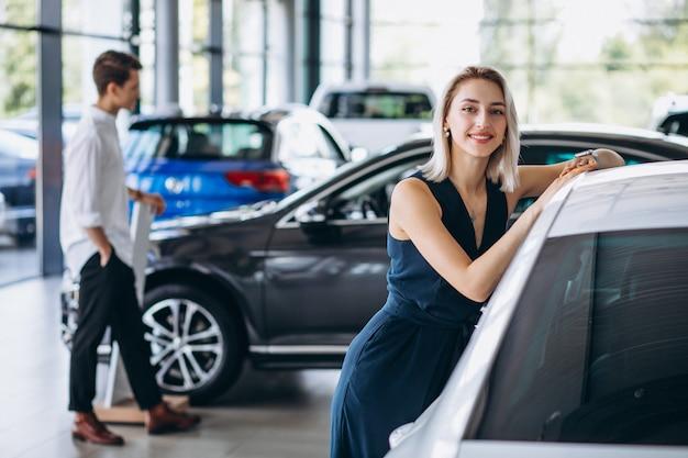 Jeune couple choisissant une voiture dans un salon automobile Photo gratuit
