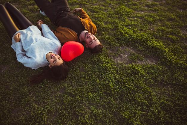 Jeune Couple Couché Sur L'herbe Avec Ballon Coeur Rouge Photo gratuit