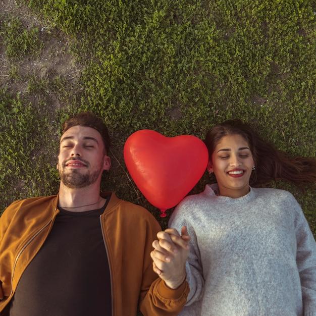Jeune Couple, Coucher Herbe, à, Ballon Coeur Photo gratuit