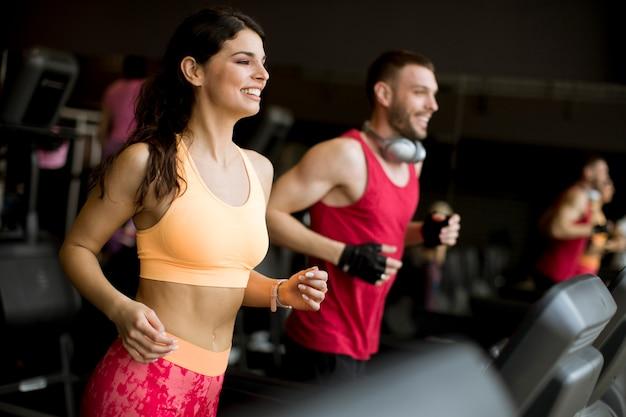 Jeune couple en cours d'exécution sur des tapis roulants dans une salle de sport moderne Photo Premium