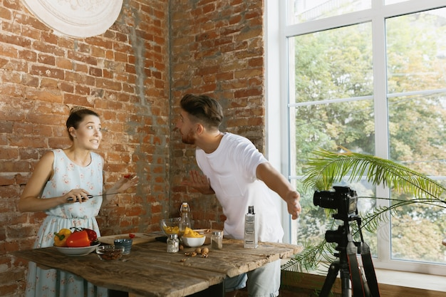 Jeune Couple Cuisinant Et Enregistrant Une Vidéo En Direct Pour Vlog Et Médias Sociaux Photo gratuit