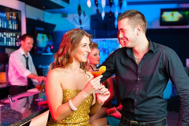 Jeune couple dans un bar ou un club buvant des cocktails Photo Premium