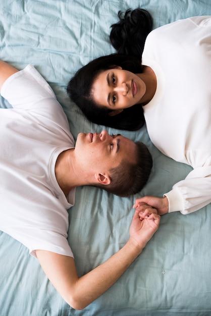 Jeune couple, dans, blanc, vêtements, coucher lit tête tête tête, et, tenant mains Photo gratuit