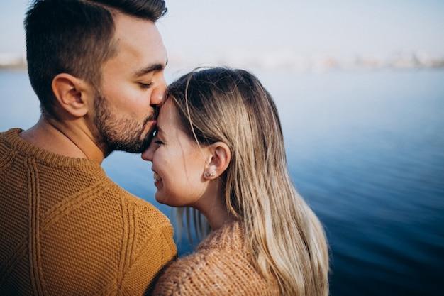 Jeune couple dans un parc debout près de la rivière Photo gratuit