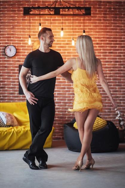 Jeune couple dansant des musiques latines: bachata, merengue, salsa. deux élégance pose sur un café avec des murs de briques Photo Premium