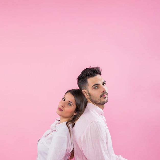 Jeune couple, debout, dos à dos Photo gratuit