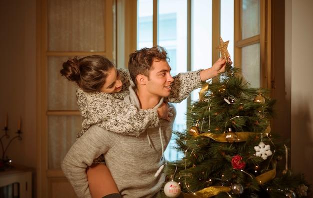 Jeune couple décorer un sapin de noël Photo gratuit