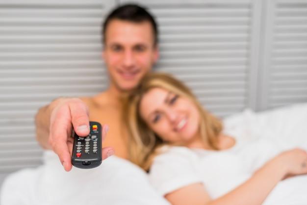 Jeune couple devant la télé au lit Photo gratuit