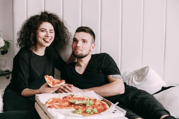 Un jeune couple drôle mange une pizza couchée sur le lit Photo gratuit