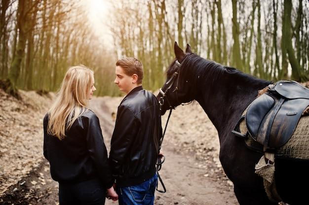 Jeune couple élégant en amour près de cheval dans la forêt d'automne Photo Premium