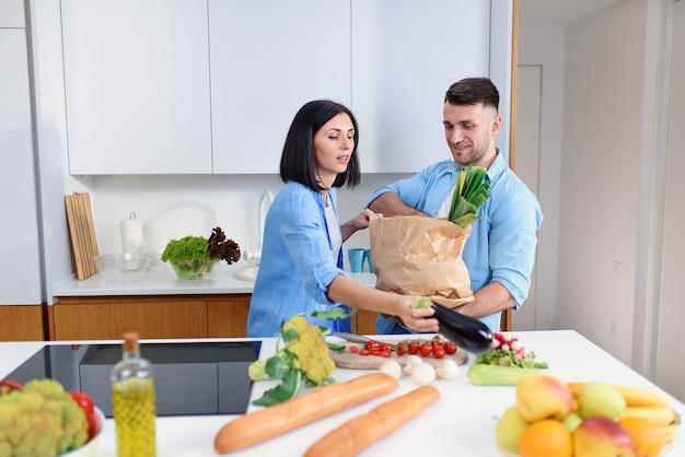 Jeune Couple élégant Déballant Ensemble Des Produits Frais Du Marché Dans Une Cuisine Confortable. Photo Premium