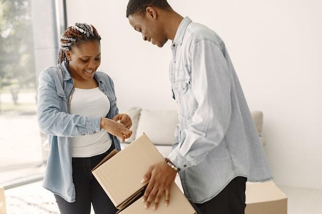 Jeune Couple Emménageant Dans Une Nouvelle Maison Ensemble. Couple Afro-américain Avec Des Boîtes En Carton. Photo gratuit