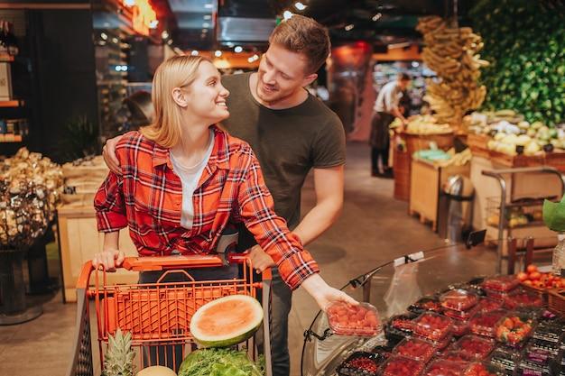 Jeune Couple En épicerie Poussant Le Graphique Photo Premium