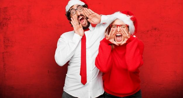 Jeune couple exprimant le concept de noël. couple et fond dans différentes couches Photo Premium