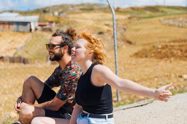 Jeune couple faisant de l'auto-stop sur le bord de la route Photo gratuit