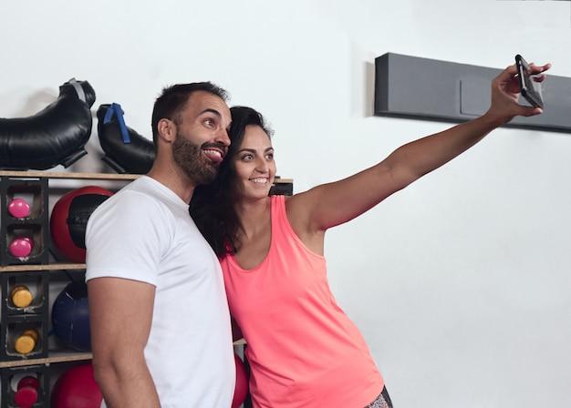 Jeune Couple Faisant Un Selfie Au Gymnase. Elle Sourit Alors Qu'il Sort Sa Langue En Faisant Des Grimaces. Photo Premium