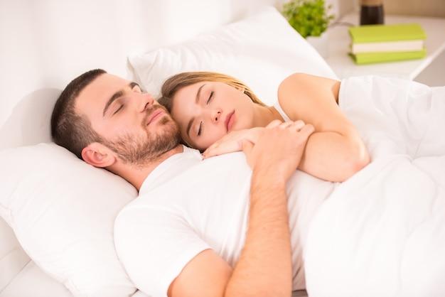 Jeune couple fatigué au lit à la maison ensemble. Photo Premium