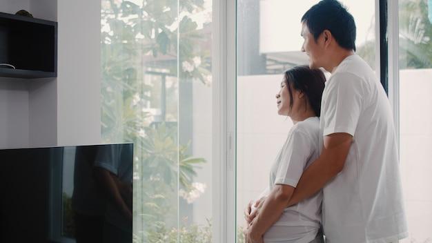 Jeune couple de femmes enceintes asiatiques étreignent et tenant le ventre en discutant avec leur enfant. maman et papa se sentent heureux, souriants, paisibles, tout en prenant soin de leur bébé, grossesse près de la fenêtre dans le salon de la maison. Photo gratuit