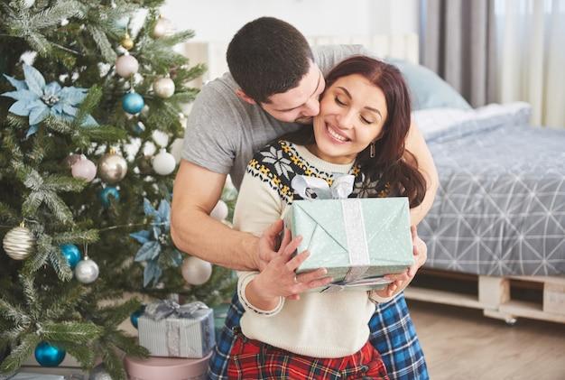 Jeune couple fête noël. un homme a soudainement présenté un cadeau à sa femme. le concept de bonheur et de bien-être familial Photo Premium