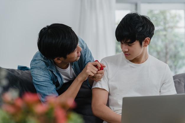 Jeune couple gay asiatique propose à la maison moderne, les hommes lgbtq coréens adolescents souriants heureux ont un temps romantique tout en proposant et alliance surprise porter bague de mariage dans le salon à la maison. Photo gratuit