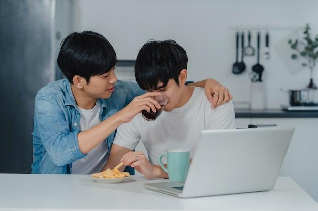 Jeune couple gay nourrir nourriture et collation à l'aide d'ordinateur portable à la maison moderne. les hommes lgbtq asiatiques heureux se détendent en utilisant les médias sociaux technologiques tout en restant assis à table dans la cuisine de la maison. Photo gratuit