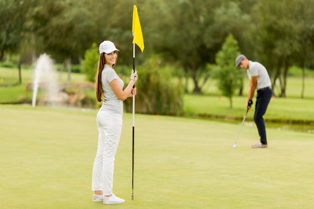 Jeune couple, golf jouant Photo Premium