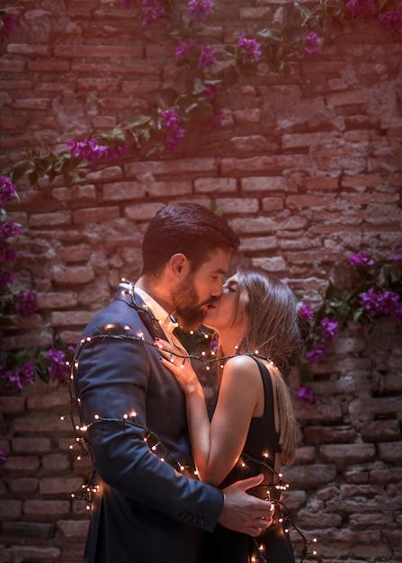 Jeune couple en guirlande s'embrasser Photo gratuit