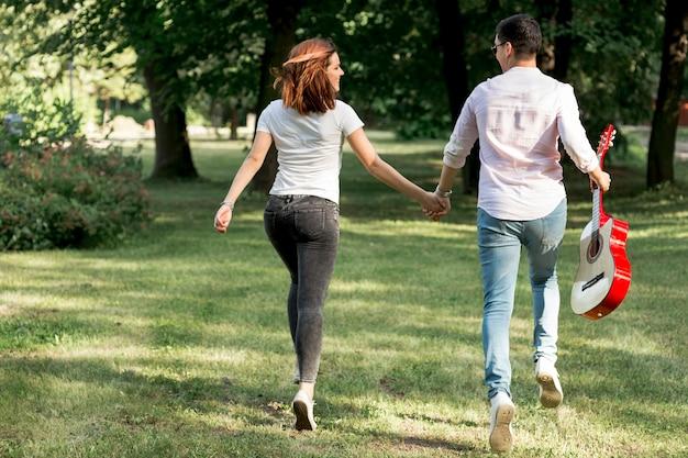 Jeune couple avec une guitare s'éloignant Photo gratuit