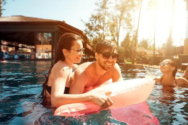 Jeune couple heureux au repos sur un matelas pneumatique dans la piscine Photo Premium
