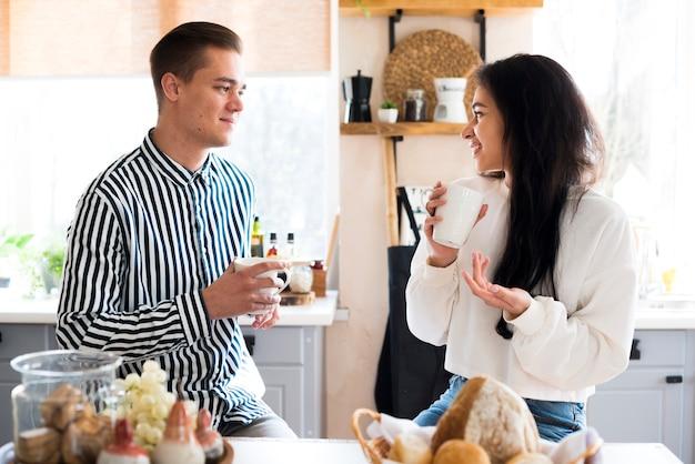 Jeune couple heureux, boire des boissons et parler Photo gratuit