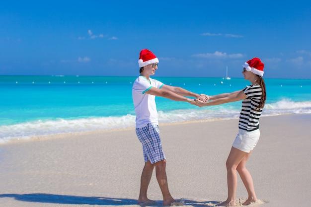 Jeune couple heureux en chapeaux rouges sur la plage blanche Photo Premium