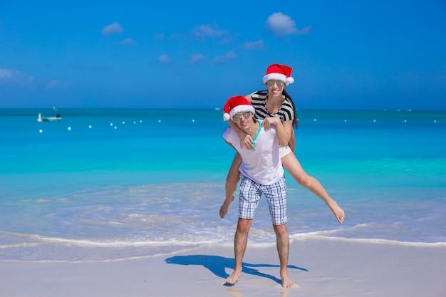 Jeune couple heureux en chapeaux rouges de santa pendant leurs vacances tropicales Photo Premium