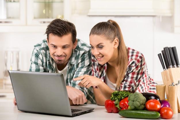Jeune couple heureux cherche une recette. Photo Premium