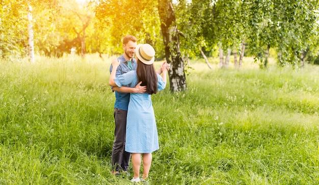 Jeune couple heureux danser dans une journée ensoleillée dans la nature Photo gratuit