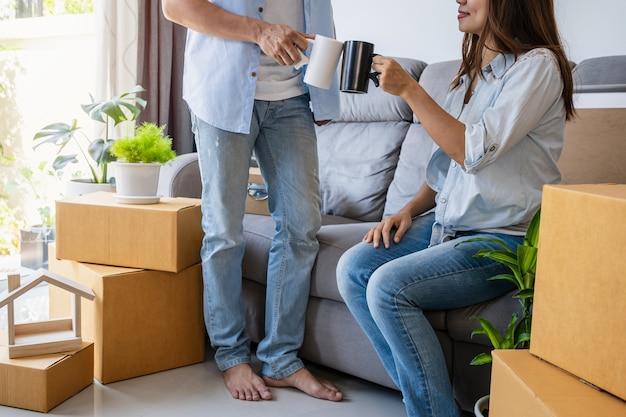Jeune Couple Heureux Se Déplaçant Dans La Nouvelle Maison Assis Et Se Détendre Sur Le Canapé Photo Premium