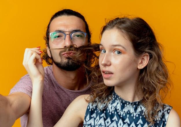 Jeune Couple Homme Et Femme Homme Imitant La Moustache Avec Les Cheveux De Sa Petite Amie Sur Mur Orange Photo gratuit