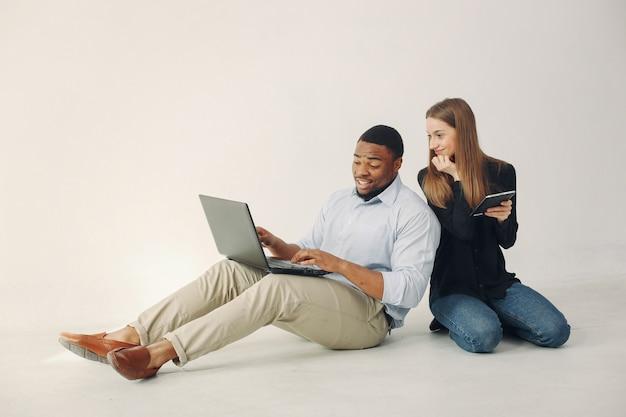 Jeune Couple International Travaillant Ensemble Et Utilisant L'ordinateur Portable Photo gratuit