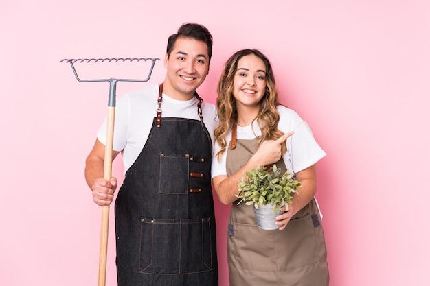 Jeune Couple Jardinier Isolé Souriant Et Pointant De Côté, Montrant Quelque Chose à L'espace Vide. Photo Premium