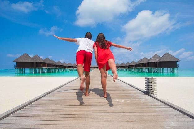 Jeune Couple Sur La Jetée De La Plage Tropicale à L'île Parfaite Photo Premium